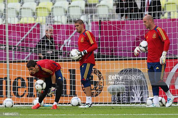 Goalkeeper Iker Casillas of Spain catches a ball ahead of Victor Valdes and Pepe Reina during a UEFA EURO 2012 training session ahead of their Group...