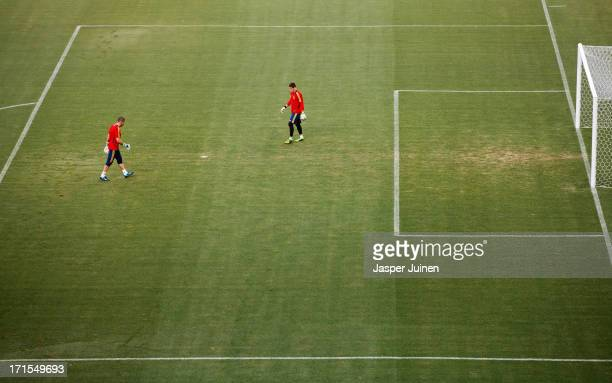 Goalkeeper Iker Casillas of Spain walks towards his teammate Victor Valdes during a training session ahead of their FIFA Confederations Cup Brazil...
