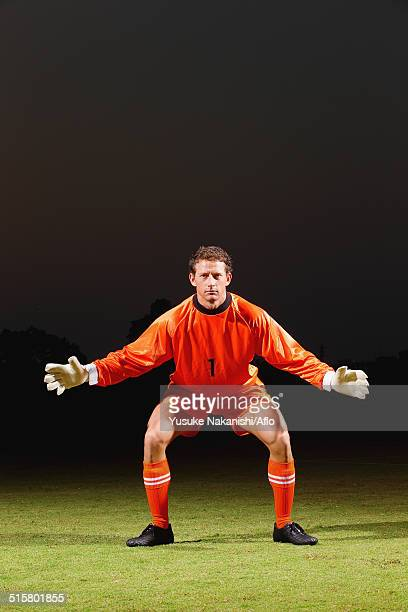 Goalkeeper in orange uniform standing in soccer field