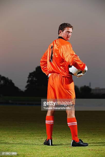 Goalkeeper in orange uniform standing in soccer field