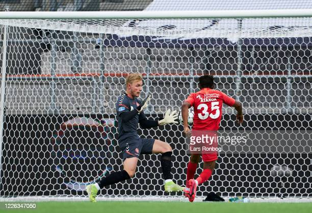 Goalkeeper Jacob Rinne of AaB Aalborg saves the ball in front of Isaac Atanga of FC Nordsjalland during the Danish 3F Superliga match between FC...