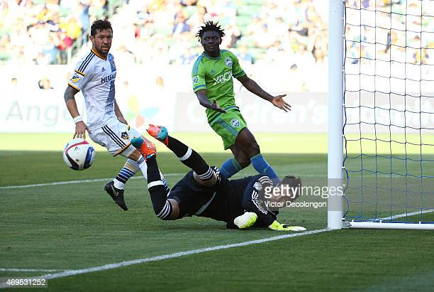 Goalkeeper Jaime Penedo of Los Angeles Galaxy makes a save as teammate Dan Gargan marks Obafemi Martins of Seattle Sounders FC in the second half of...