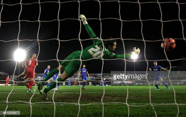 Goalkeeper James Shea of AFC Wimbledon dives in vain as Steven Gerrard of Liverpool scores the opening goal with a header during the FA Cup Third...