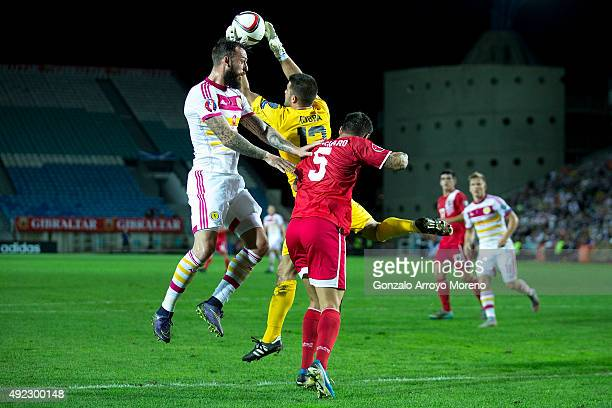 Goalkeeper Jamie Robba of Gibraltar stops the ball with his teammate Ryan Casciaro against Steven Fletcher of Scotland during the UEFA EURO 2016...