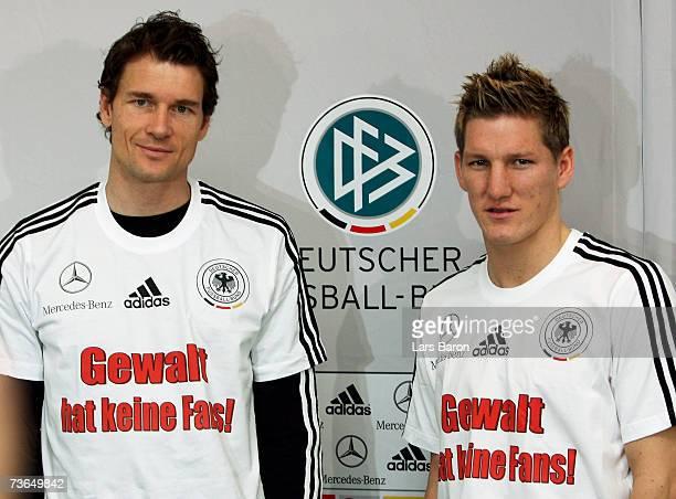 Goalkeeper Jens Lehmann and Bastian Schweinsteiger pose with a jersey that reads 'Gewalt hat keine Fans' during the German National Football team...