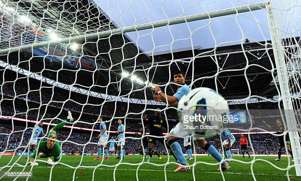 Goalkeeper Joe Hart and Sergio Aguero of Manchester City look on in vain as the header from Ben Watson of Wigan Athletic hits the back of the net for...