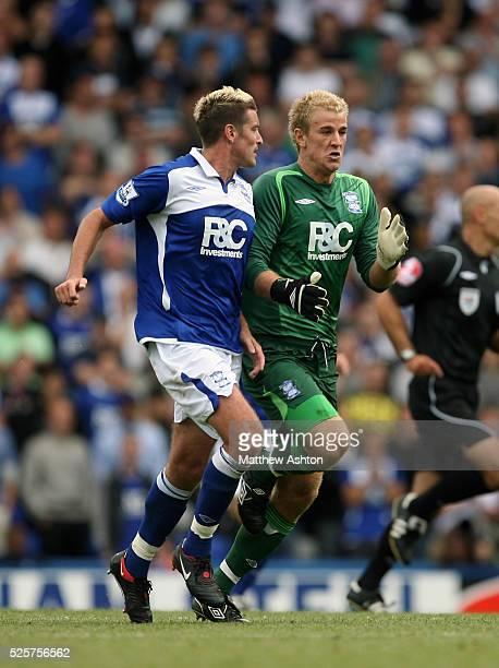 Goalkeeper Joe Hart of Birmingham City bumps into Franck Queudrue of Birmingham City as he races back to his goal