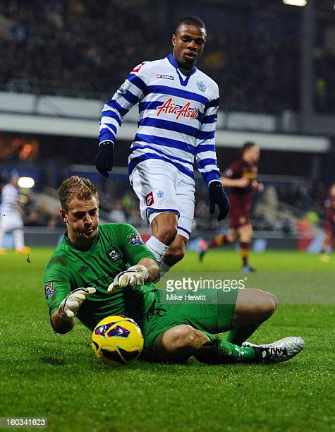 Goalkeeper Joe Hart of Manchester City smothers the ball as Stephane Mbia of QPR closes in during the Barclays Premier League match between Queens...