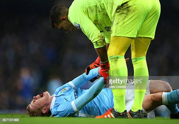 Goalkeeper Joel Robles of Everton attempts to assist the injured Kevin De Bruyne of Manchester City during the Capital One Cup Semi Final second leg...