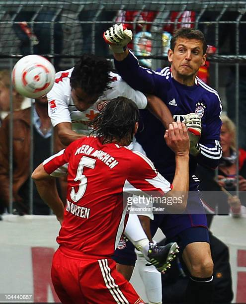 Goalkeeper Joerg Butt and Daniel van Buyten of Muenchen head for the ball with Sami Allagui of Mainz during the Bundesliga first league match between...