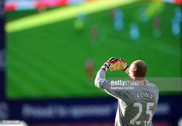 Goalkeeper Jose Manuel Reina of Liverpool watches the game against a backdrop of a huge television screen