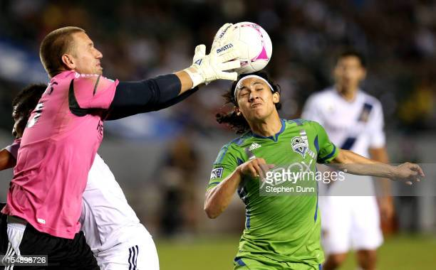 Goalkeeper Josh Saunders of the Los Angeles Galaxy knocks the ball away from Fredy Montero of the Seattle Sounders at The Home Depot Center on...