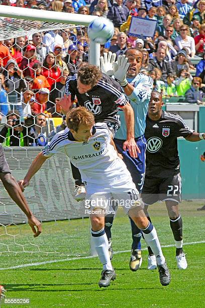 Goalkeeper Josh Wicks and midfielder Ben Olsen of DC United leap to stop a loose ball over Mike Magee of the Los Angeles Galaxy during their MLS game...