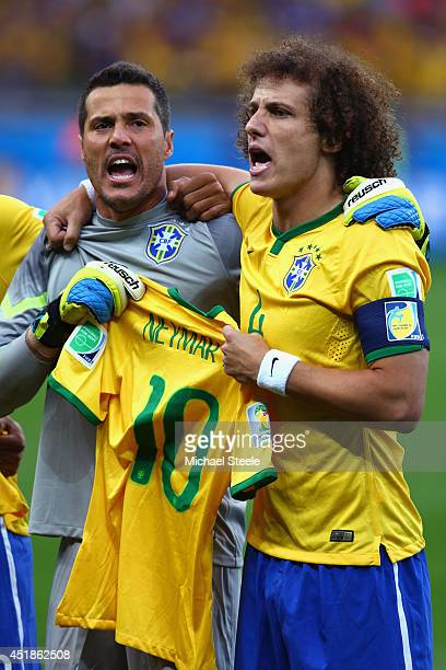 Goalkeeper Julio Cesar and David Luiz of Brazil hold a Neymar jersey as they sing the National Anthem prior to the 2014 FIFA World Cup Brazil Semi...