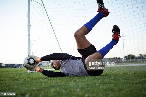 Goalkeeper jumping out to catch football