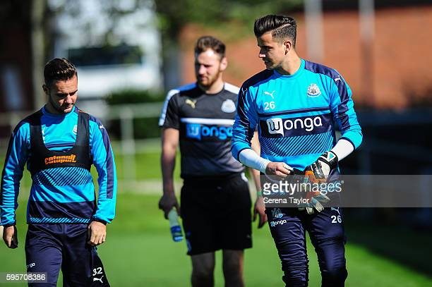 Goalkeeper Karl Darlow puts on his gloves as he walks outside with teammate Adam Armstrong during the Newcastle United Training Session at The...