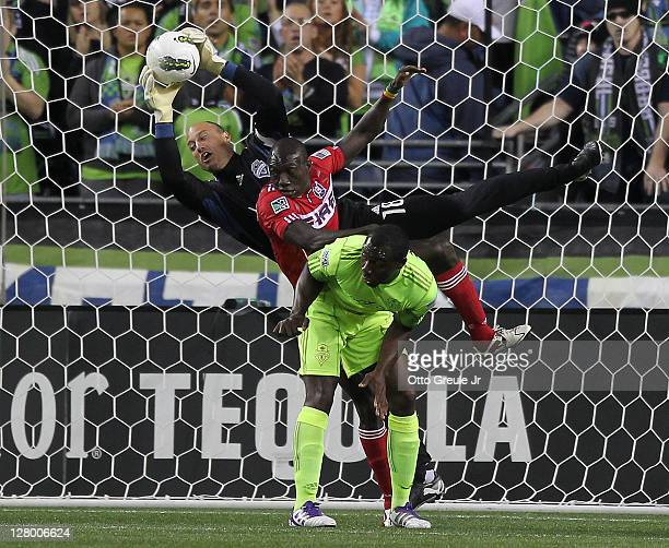 Goalkeeper Kasey Keller of the Seattle Sounders FC blocks a shot behind Dominic Oduro of the Chicago Fire as Jhon Kennedy Hurtado looks on in the...
