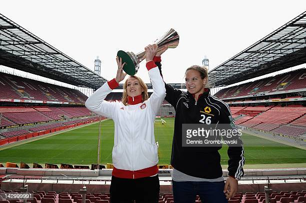 Goalkeeper Kathrin Laengert of Muenchen and Desiree Schumann of Frankfurt pose with the Women's DFB Cup trophy during the Women's DFB Cup Final press...