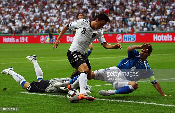 Goalkeeper Kenan Hasagic and Emir Spahic of Bosnia tackle Mesut Oezil of Germany during the international friendly match between Germany and...