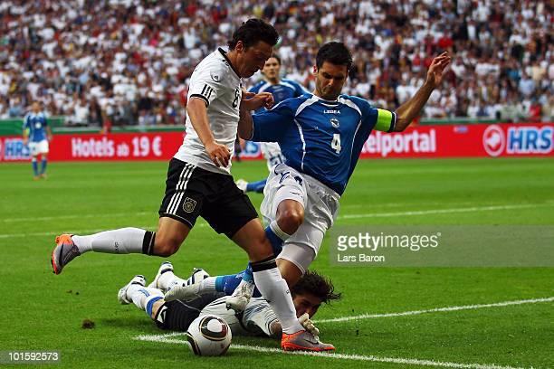Goalkeeper Kenan Hasagic of Bosnia tackles Mesut Oezil of Germany during the international friendly match between Germany and Bosnia-Herzegovina at...