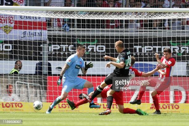 Goalkeeper Kevin Mueller of FC Heidenheim, Holger Badstuber of VfB Stuttgart and Patrick Mainka of FC Heidenheim scores his team's second goal during...