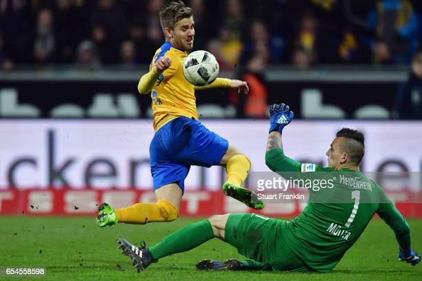Goalkeeper Kevin Mueller of Heidenheim makes a save against Christoffer Nyman of Braunschweig during the Second Bundesliga match between Eintracht...