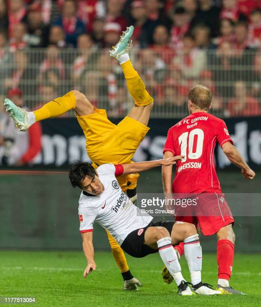 Goalkeeper Kevin Trapp of Eintracht Frankfurt tries to save the ball as he jumps over Makoto Hasebe of Eintracht Frankfurt and Sebastian Andersson of...