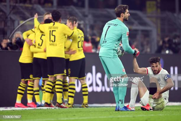 Goalkeeper Kevin Trapp of Frankfurt helps up David Abraham as Erling Haland of Dortmund celebrates his team's third goal with team mates during the...