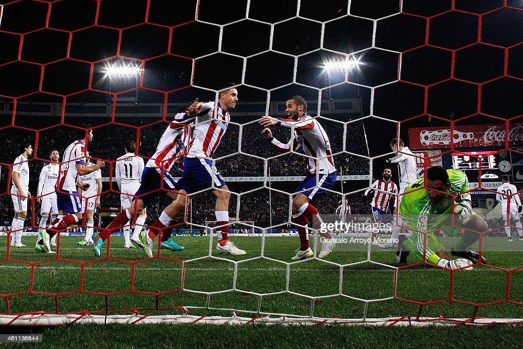 goalkeeper Keylor Navas (R) of Real Madrid CF stands form the ground as Jose Maria Gimenez (L) of Atletico de Madrid celebrates scoring their second goal with teammates during the Copa del Rey Round of 16 first leg match between Club Atletico de Madrid and Real Madrid CF at Vicente Calderon Stadium on January 7, 2015 in Madrid, Spain.