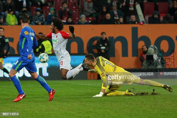 Goalkeeper Koen Casteels of Wolfsburg and Francisco da Silva Caiuby of Augsburg in action during the Bundesliga match between FC Augsburg and VfL...