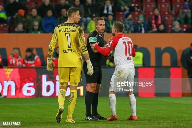 Goalkeeper Koen Casteels of Wolfsburg looks on and Referee Tobias Stieler speaks with Daniel Baier of Augsburg during the Bundesliga match between FC...