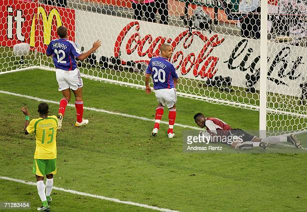 Goalkeeper Kossi Agassa of Togo clutches the ball as David Trezeguet and Thierry Henry of France look dejected during the FIFA World Cup Germany 2006...