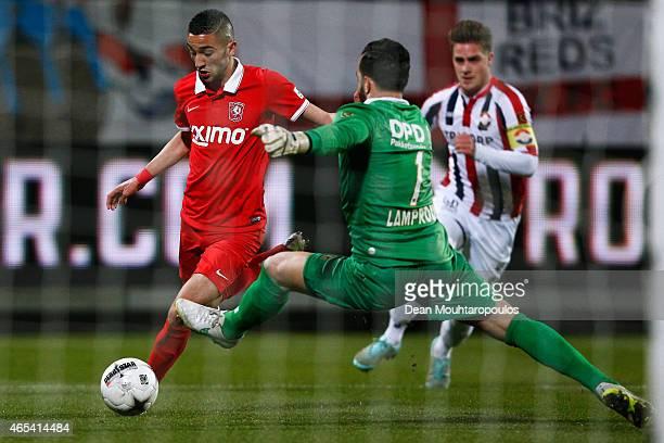 Goalkeeper Kostas Lamprou of Willem II attempts the block as Hakim Ziyech of Twente shoots on goal during the Dutch Eredivisie match between Willem...