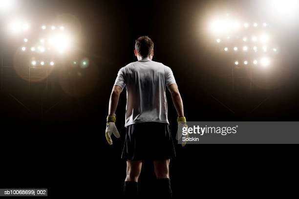 goalkeeper looking at stadium light, rear view - portiere posizione sportiva foto e immagini stock