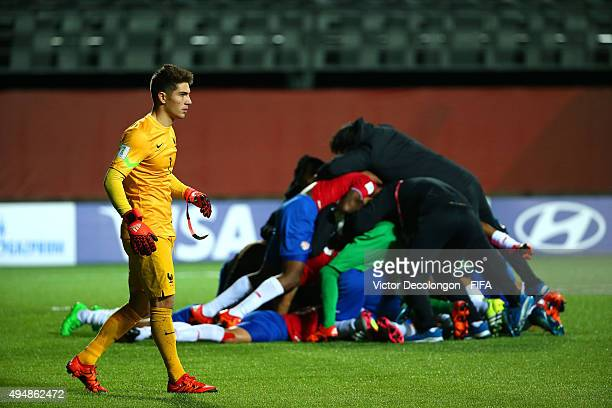 Goalkeeper Luca Zidane of France walks by Costa Rica players while they celebrate their 53 penatly kick shootout win in the France v Costa Rica Round...