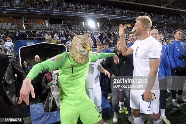 Goalkeeper Lukas Hradecky of Finland wears a mask of an eagle owl as he celebrates with Paulus Arajuuri after the UEFA Euro 2020 Group J...
