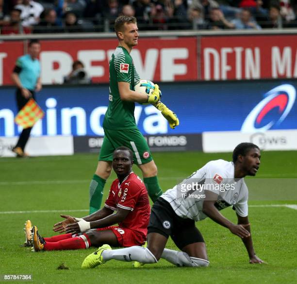 Goalkeeper Lukas Hradecky of Frankfurt and Chadrac Akolo of Stuttgart and Taleb Tawatha of Frankfurt battle for the ball during the Bundesliga match...