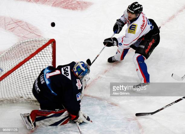 Goalkeeper Lukas Lang of Mannheim is challenged by Bob Wren of Ingolstadt during the DEL match between Adler Mannheim and ERC Ingolstadt at the SAP...