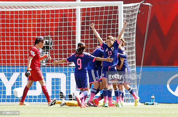 Goalkeeper Lydia Williams of Australia walks behind Nahomi Kawasumi and Rumi Utsugi of Japan as they celebrate their team's goal during the FIFA...
