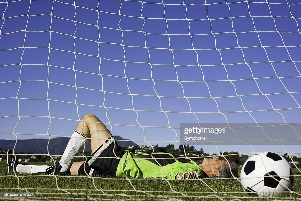Goalkeeper lying on grass with ball in net, side view : Stockfoto