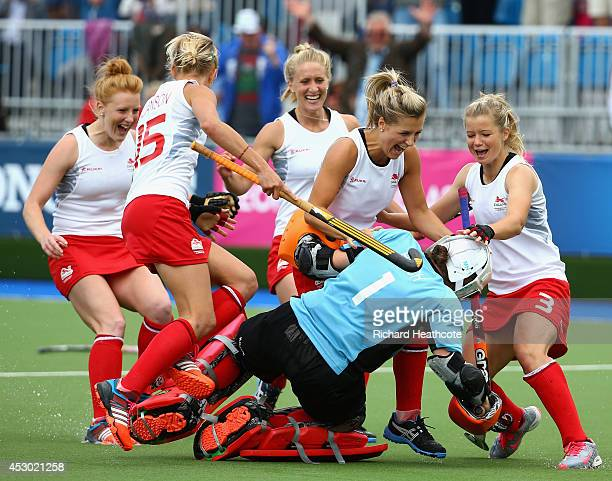 Goalkeeper Maddie Hinch of England is mobbed by her teammates as she saves the deciding penalty shuttle to put England through to the Gold Medal...