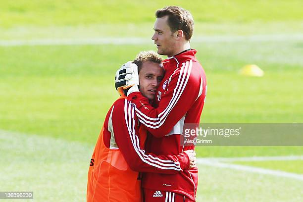 Goalkeeper Manuel Neuer hugs team mate Rafinha during a training session of Bayern Muenchen at the ASPIRE Academy for Sports Excellence on January 4...