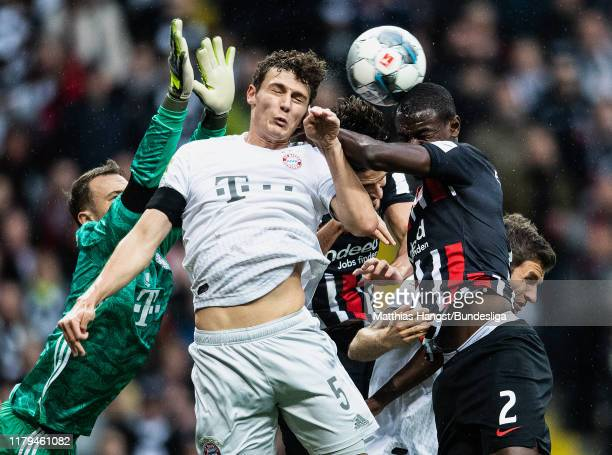 Goalkeeper Manuel Neuer of FC Bayern München in action against Evan NDicka of FRankfurt and Benjamin Pavard of FC Bayern München during the...