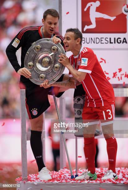 Goalkeeper Manuel Neuer of FC Bayern Muenchen and Rafinha of FC Bayern Muenchen lift the Championship trophy in celebration of the 67th German...