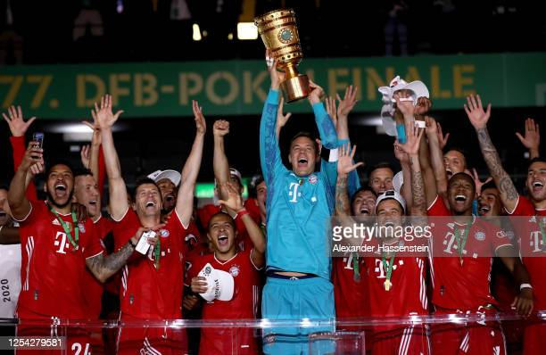 Goalkeeper Manuel Neuer of FC Bayern Muenchen lifts the trophy in celebration with his team mates after the DFB Cup final match between Bayer 04...