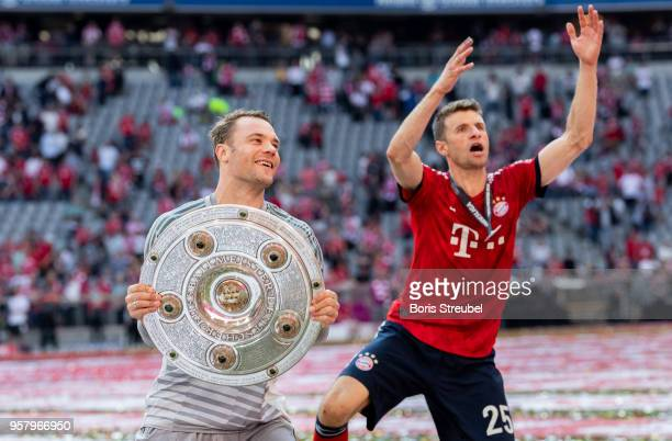 Goalkeeper Manuel Neuer of FC Bayern Muenchen lifts the trophy to celebrate the 28th German football championship after the Bundesliga match between...