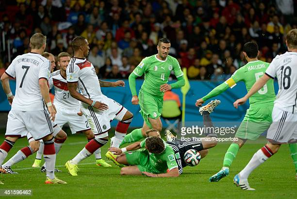 Goalkeeper Manuel Neuer of Germany falls to the ground with Mehdi Mostefa of Algeria during the 2014 FIFA World Cup Brazil Round of 16 match between...
