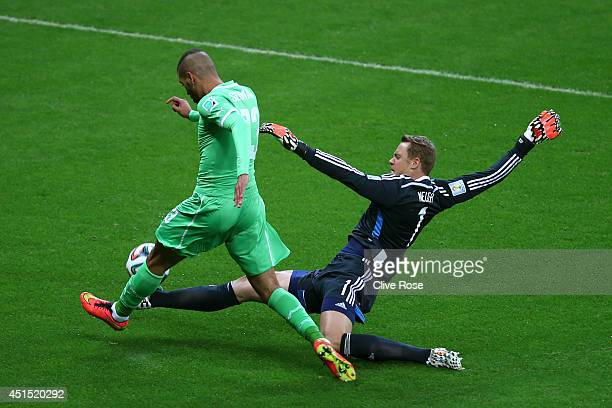 Goalkeeper Manuel Neuer of Germany tackles Islam Slimani of Algeria during the 2014 FIFA World Cup Brazil Round of 16 match between Germany and...