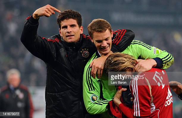 Goalkeeper Manuel Neuer of Muenchen celebrates with team mates Mario Gomez and Anatoliy Tymoshchuk after winning the DFB Cup semi final match between...
