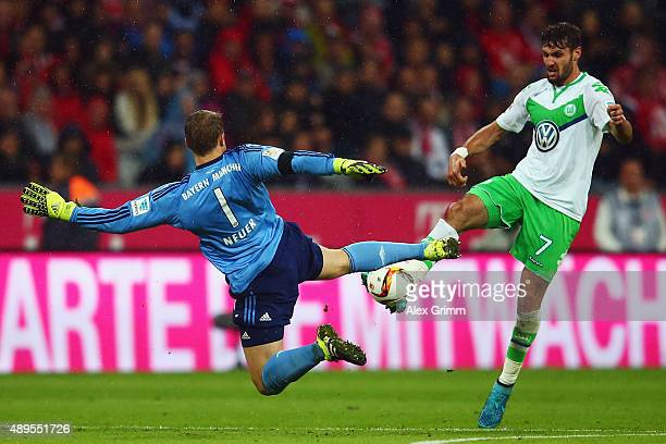 Goalkeeper Manuel Neuer of Muenchen is challenged by Daniel Caligiuri of Wolfsburg during the Bundesliga match between FC Bayern Muenchen and VfL...